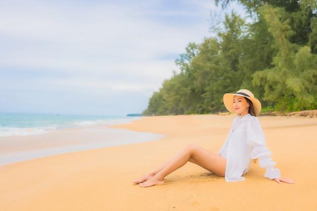 Портрет красивой молодой азиатской женщины ослабляя вокруг океана моря пляжа в каникулах перемещения