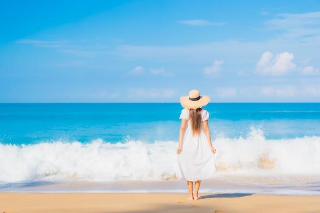 旅行休暇で青い空に白い雲とビーチの周りでリラックスした美しい若いアジアの女性の肖像画