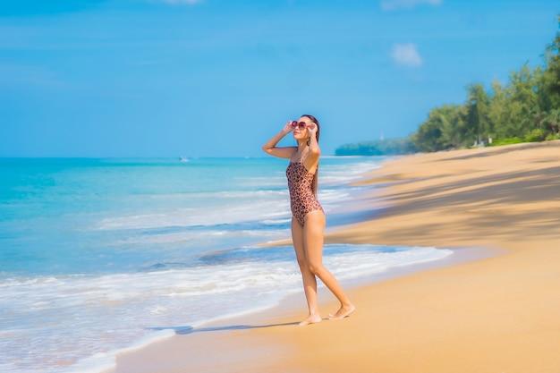 Портрет красивой молодой азиатской женщины ослабляя вокруг пляжа с белыми облаками на голубом небе в каникулах перемещения