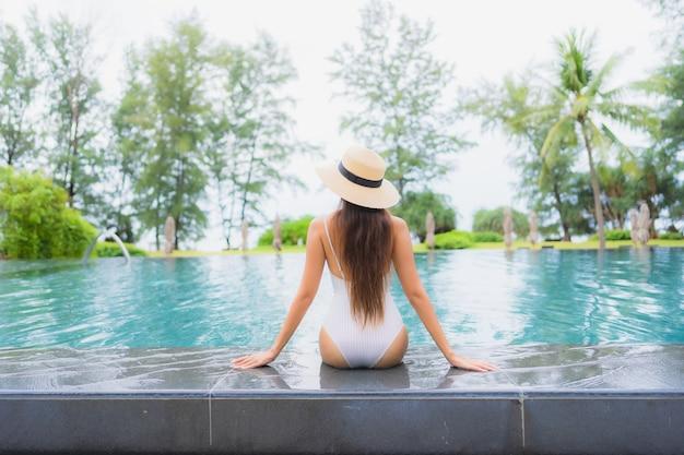 바다에 가까운 호텔 리조트에서 야외 수영장 주변에서 편안한 아름 다운 젊은 아시아 여자의 초상화
