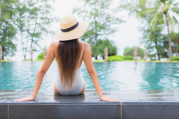 ほぼ海のホテルリゾートの屋外スイミングプールの周りでリラックスした美しい若いアジアの女性の肖像画