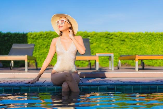 호텔 리조트에서 야외 수영장 주변에서 편안한 아름 다운 젊은 아시아 여자의 초상화