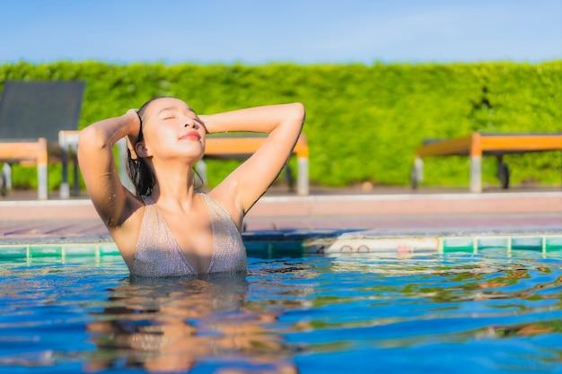 ホテルリゾートの屋外スイミングプールの周りでリラックスした美しい若いアジアの女性の肖像画