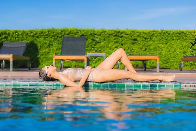 Портрет красивой молодой азиатской женщины ослабляя вокруг открытого бассейна в курорте гостиницы