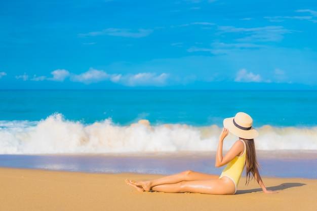 Портрет красивой молодой азиатской женщины ослабляя на пляже в каникулах перемещения