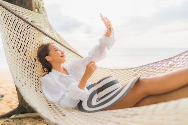 Портрет красивой молодой азиатской женщины ослабляя на гамаке вокруг пляжа в отпуске