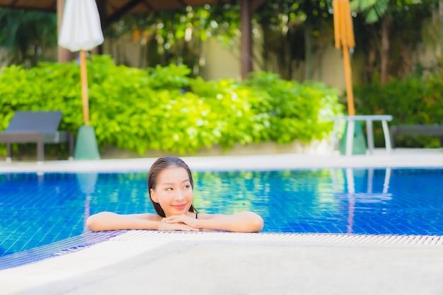 Портрет красивой молодой азиатской женщины расслабляя вокруг открытого бассейна в курорте гостиницы