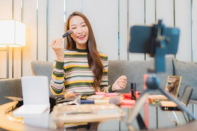 美しい若いアジアの女性の肖像画は、ソファの上の化粧品をレビューし、使用しています