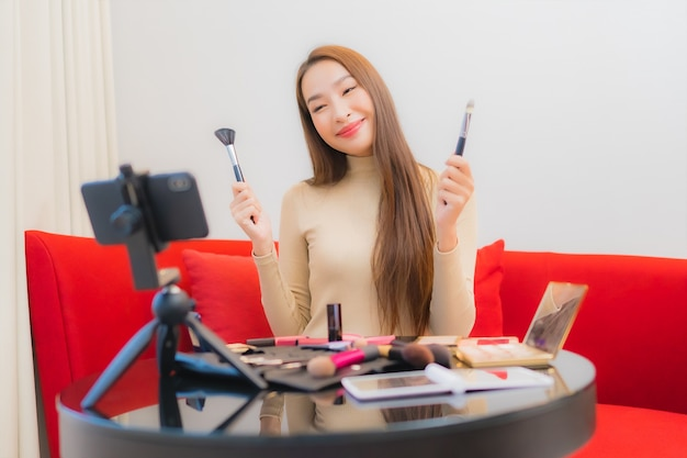 아름 다운 젊은 아시아 여자의 초상화 리뷰 및 소파에 화장품을 사용