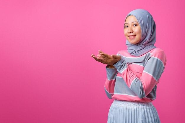 ピンクの背景に両手で製品を示す美しい若いアジアの女性の肖像画
