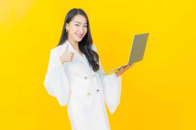 노란 벽에 컴퓨터 노트북을 들고 웃는 아름다운 젊은 아시아 여성의 초상화