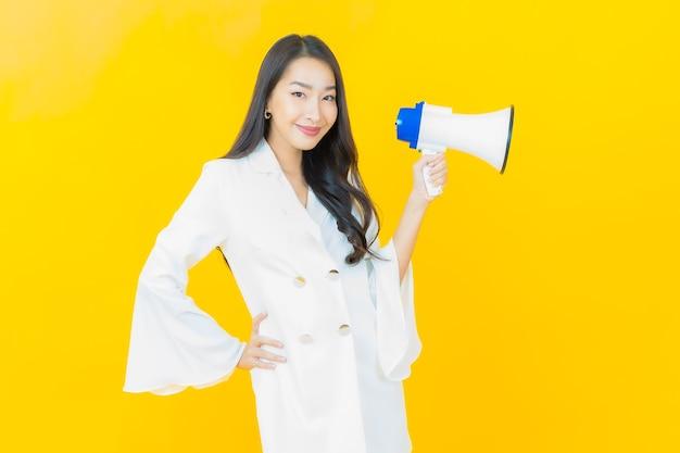노란 벽에 확성기와 함께 웃는 아름다운 젊은 아시아 여성의 초상화