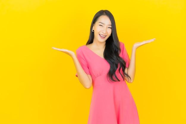 黄色の壁にピンクのドレスで笑顔の美しい若いアジアの女性の肖像画