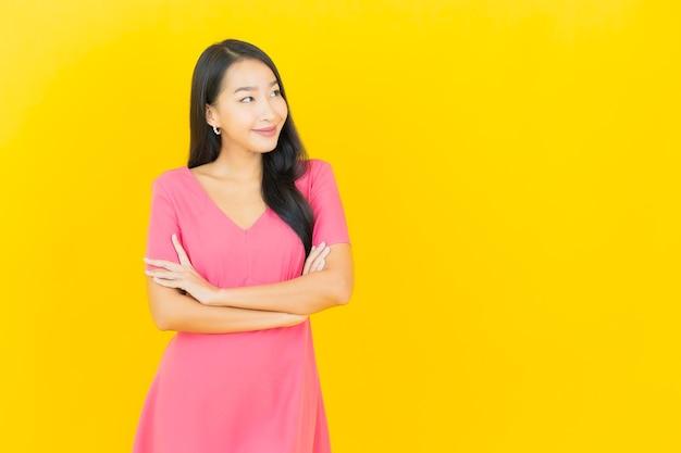 노란색 벽에 핑크 드레스에 아름 다운 젊은 아시아 여자 미소의 초상화