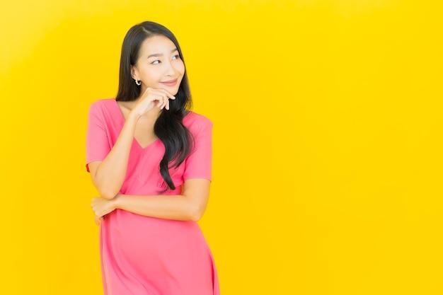 Портрет красивой молодой азиатской женщины улыбается в розовом платье на желтой стене