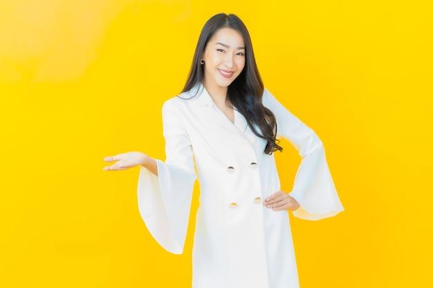 Портрет красивой молодой азиатской женщины улыбается на желтой стене