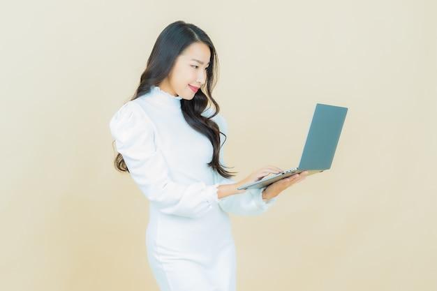 외진 벽에 컴퓨터 노트북을 들고 웃는 아름다운 젊은 아시아 여성의 초상화