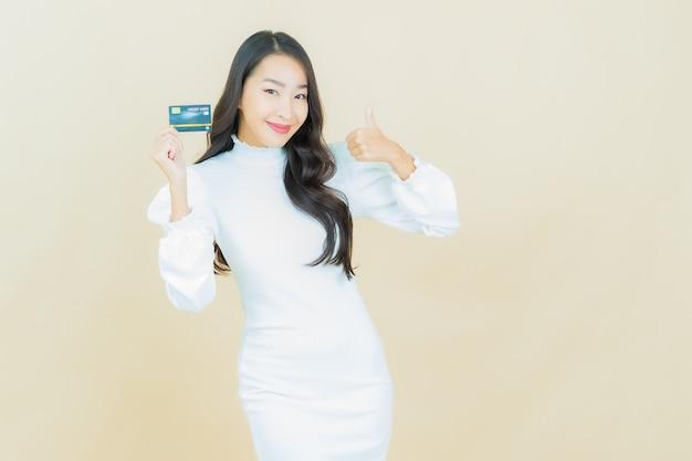 Портрет красивой молодой азиатской женщины улыбается с кредитной картой на стене цвета