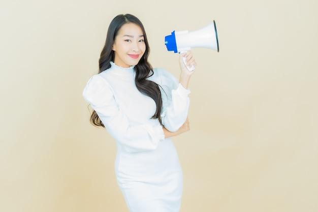 아름다운 젊은 아시아 여성의 초상화는 색 벽에 확성기를 들고 웃는다