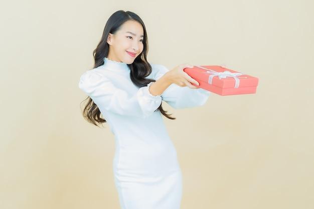 컬러 벽에 빨간 선물 상자를 들고 웃는 아름다운 젊은 아시아 여성의 초상화