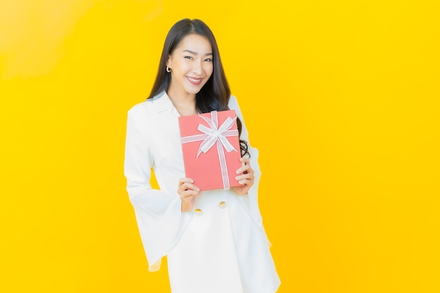 Портрет красивой молодой азиатской женщины улыбается с красной подарочной коробкой на желтой стене
