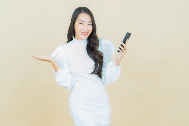 아름다운 젊은 아시아 여성의 초상화는 컬러 벽에 스마트 휴대전화로 웃고 있다