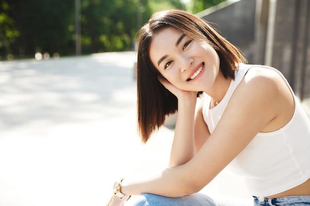 ベンチに座って外で笑っている美しい若いアジアの女性の肖像画