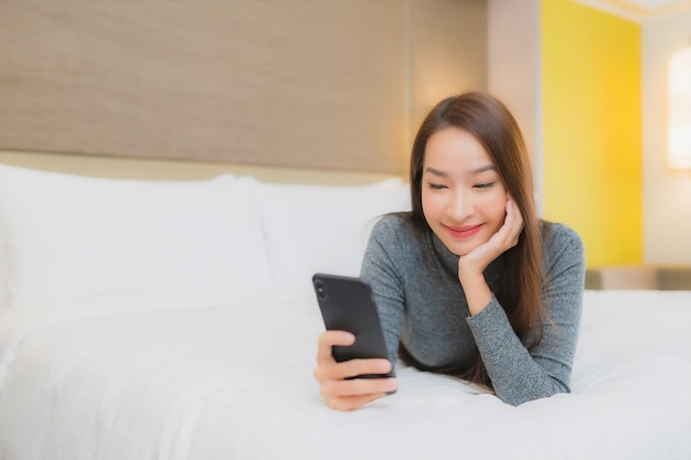 Портрет красивой молодой азиатской женщины использует смартфон на кровати