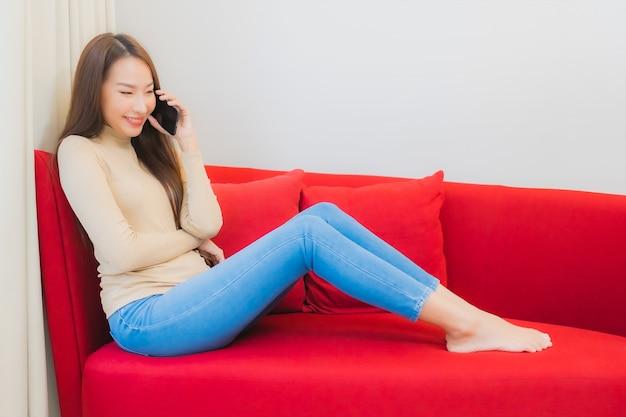 美しい若いアジアの女性の肖像画は、リビングルームのインテリアのソファでスマートフォンを使用しています