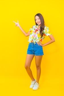 カラフルなシャツを着て、黄色の壁に指で撮影する美しい若いアジアの女性の肖像画