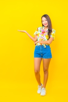 화려한 셔츠를 입고 노란색 벽에 뭔가 보여주는 아름다운 젊은 아시아 여자의 초상화