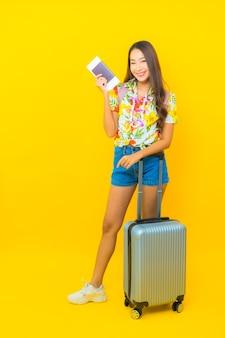 Портрет красивой молодой азиатской женщины в красочной рубашке с багажом и билетами на самолет, готовыми к путешествию