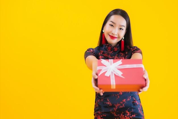 아름 다운 젊은 아시아 여자의 초상화는 중국 드레스를 입고 빨간색 선물 상자를 개최