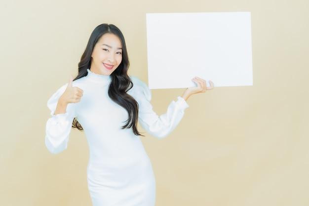 컬러 벽에 빈 흰색 광고판이 있는 아름다운 젊은 아시아 여성의 초상화