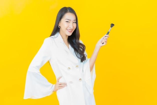 노란 벽에 화장용 브러시를 바른 아름다운 젊은 아시아 여성의 초상화