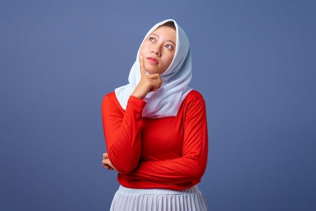 Портрет красивой молодой азиатской женщины с выражением мышления на сером фоне