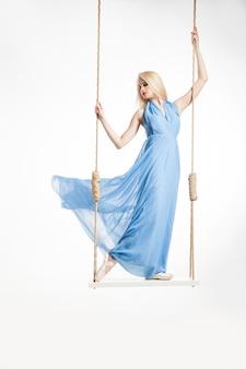 파란 드레스와 pointes.isolated 그네에 서 있는 아름 다운 젊은 발레리 나의 초상화.