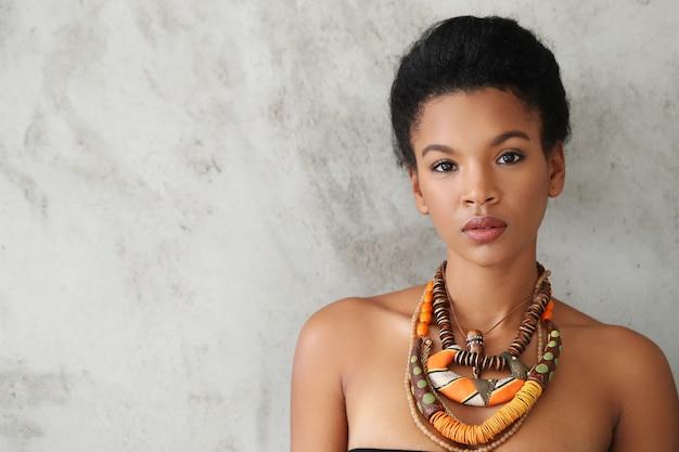 전통적인 아프리카 목걸이와 아름 다운 젊은 흑인 여자의 초상화