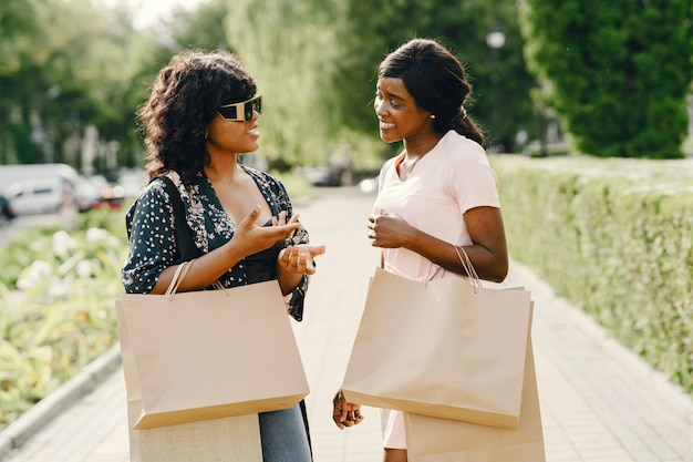 Портрет красивых молодых чернокожих женщин с хозяйственными сумками