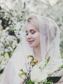 公園でエレガントなドレスを着た美しい若い金髪の花嫁の肖像画。