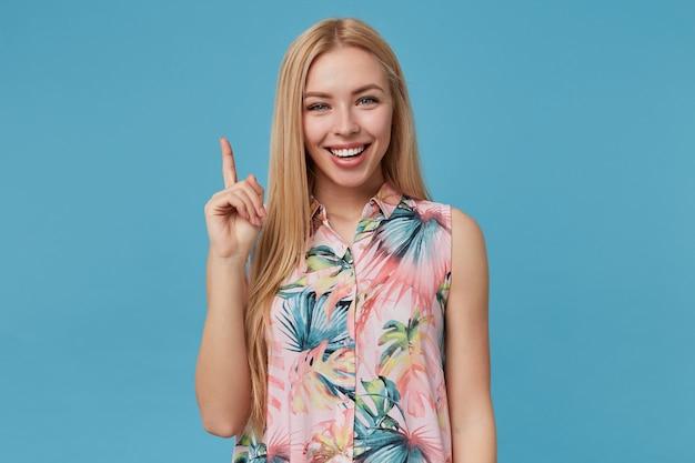 꽃이 만발한 로맨틱 드레스 포즈에서 아름 다운 젊은 금발 여성의 초상화, 집게 손가락으로 위쪽으로 표시하고 넓은 밝은 미소로보고