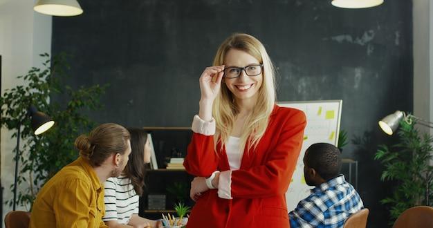 メガネの手を交差し、教室でカメラに笑顔で美しい若いブロンドの女の子の肖像画。