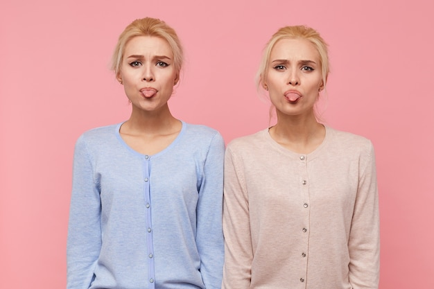 ピンクの背景の上に分離されたカメラを見て、美しい若い金髪の双子の肖像画は顔を作り、舌を表示します。