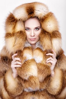 럭셔리 폭스 모피 코트에 아름 다운 젊은 금발 여자의 초상화. 회색 배경에 겨울 패션
