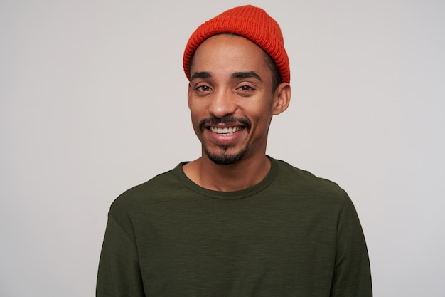 Портрет красивого молодого кареглазого темнокожего мужчины с бородой, весело смотрящего с приятной улыбкой, одетого в красную шляпу и пуллон цвета хаки на белом