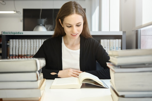 Портрет красивой молодой брюнетки-профессора в черной куртке, читающей пособие или учебник, улыбаясь, готовясь к лекции в университете, сидя в библиотеке перед стопками книг
