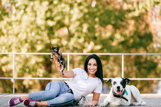 小さな猫と公園で屋外に座っている大きなハウンド犬と美しい若いブルネットの少女の肖像画