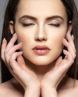 きれいな顔を持つ美しい若いブルネットの女性の肖像画。落ち着いた顔。目を閉じた可愛らしいモデル。瞑想