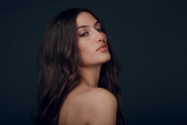 Портрет красивой молодой женщины брюнет с здоровыми волосами.