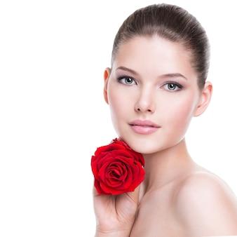 顔の近くに赤いバラを持つ美しい若いブルネットの女性の肖像画-白で隔離。